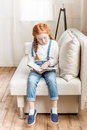 Redhead little girl sitting on sofa and reading book Royalty Free Stock Photo