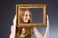 Redhead with picture frame against dark background Royalty Free Stock Image