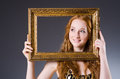 Redhead with picture frame against dark background Royalty Free Stock Photo