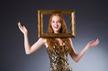 Redhead with picture frame against dark background Stock Photography