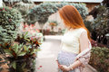 Redhead pregnant girl stroking her belly. On the background of the yard with plants. Summer Royalty Free Stock Photo