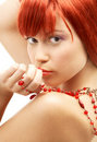 Redhead with red beads looking Royalty Free Stock Photography