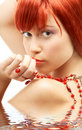 Redhead with red beads looking over shoulder  Royalty Free Stock Images