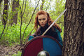 Redhead scandinavian woman young with sword and shield posing in a wood Royalty Free Stock Photography
