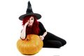Redhead witch sits leaning against a big pumpkin isolated on white background Royalty Free Stock Photo
