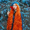Redhead woman in blue coat on flower background. Fashion model with long red hair with red flower in hand. turban and stylish coat