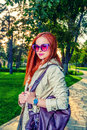Redhead woman in casual clothing posing outdoors in 60th fashion  sunglasses and bright violet handbag Royalty Free Stock Photo
