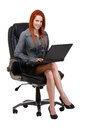 Redhead woman with laptop sitting on chair Royalty Free Stock Photos