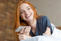 Redhead woman lying on the bed with smartphone Royalty Free Stock Photo