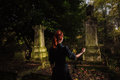 Redhead woman performing ritual at grave a or witch is raising her arms and a by a Stock Photos