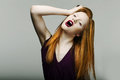 Redhead woman pulling her hair in frustration Stock Photos