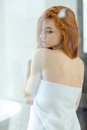 Redhead woman standing in bathroom back view portrait of a beautiful towel Stock Images