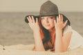 Redhead woman wearing sun hat lying on beach
