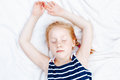 redheaded Caucasian child girl in striped nautical sleeveless shirt sleeping Royalty Free Stock Photo