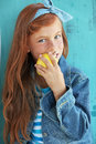 Redheaded child cute eating apple on vintage blue background Royalty Free Stock Images