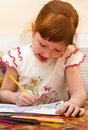 Redheaded child draws a picture Stock Photos