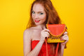 Redheaded smiling girl with orange purse Royalty Free Stock Photo