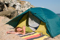 Redheaded woman sleeping in the tent at sea beach Stock Photography