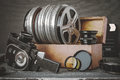 Reels with films in a wooden box, lens and an old movie camera Royalty Free Stock Photo