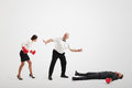 Referee holding angry businesswoman in boxer gloves and counting down to knocked out businessman over light grey background Stock Photo