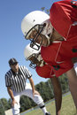 Referee watching football players on field blurred two american the Stock Images