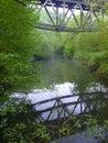 Reflecion of an iron arch bridge in a river Royalty Free Stock Photo