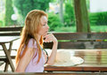 The reflected woman sits at table in summer cafe Stock Photo