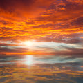 Reflection of beautiful sunset majestic clouds and sun above orange red water Royalty Free Stock Images