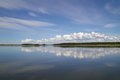 Reflection of blue sky with white clouds in water Royalty Free Stock Photo
