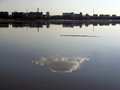 Reflection of a cloud in the water surface of a pond in the even Royalty Free Stock Photo