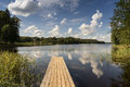 Reflection of clouds in the lake with boardwalk and trees background Royalty Free Stock Image