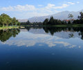 Reflection of clouds on a lake over the mountains the is surrounded by walking path with green trees and green grass Royalty Free Stock Photo