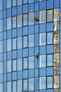 Reflection of construction crane on the glass of tall multistoried office building Royalty Free Stock Photo