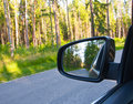 Reflection of forest in the car side mirror. Royalty Free Stock Photo