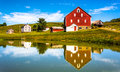 Reflection of house and barn in a small pond, in rural York Coun Royalty Free Stock Photo
