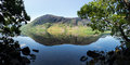 Reflection on lake district hills in crummock mirror like of the surrounding water framed by the trees the lakeside idyllic image Royalty Free Stock Photo