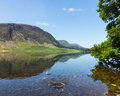 Reflection on lake district hills in crummock mirror like of the surrounding water with a splash from thrown stone spoiling the Royalty Free Stock Photo