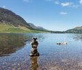 Reflection on lake district hills in crummock water mirror like of the surrounding with a stack of stones appearing like a robot Royalty Free Stock Images