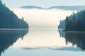 Reflection of morning fog rising on lake between mountains Royalty Free Stock Photos