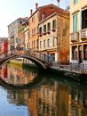 Reflection in a venice canal early morning reflections with bridge italy Stock Photo