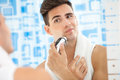 Reflection of young man in mirror shaving with electric shaver Stock Photo
