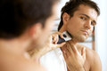Reflection of young man in mirror shaving with electric shaver Royalty Free Stock Photo
