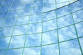 Reflections clouds blue sky facade office building Stock Image