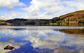 Reflections of clouds and mountain forests in pontsticill reservoir cronfa ddwr including ty cwch boat house hwylio sailing Royalty Free Stock Photos