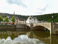 Reflections of the old stone bridge and the vintage buildings on Semois river at Bouillon Royalty Free Stock Photo