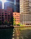 Reflections paint designs from nearby architecture onto Chicago River during summer evening while patrons enjoy happy hour Royalty Free Stock Photo