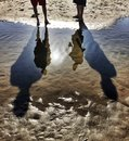 Reflections and tall shadows at the beach big in sand water of two people Stock Photo