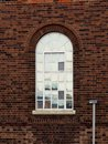 Reflective arched window this and alcoved has various panes missing and replaced with wire mesh plus is covered in a coating that Stock Image