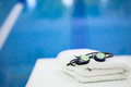 Reflective goggles beads water them sitting besides swimming pool clean white nicely folded towel Stock Photos