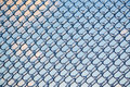 Refracted clouds and blue sky through ice on fence a shot of thick layer of partially covering a frozen metal chain link after an Royalty Free Stock Photography